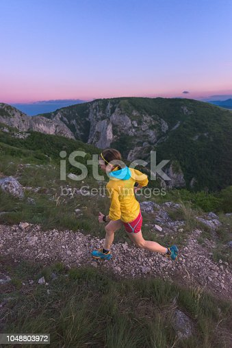 Above view of woman ultra marathonist running outdoor at sunset