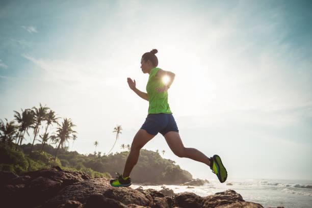 Frau Ultramarathon Trail Läufer läuft zu felsigen Berggipfel am Meer – Foto