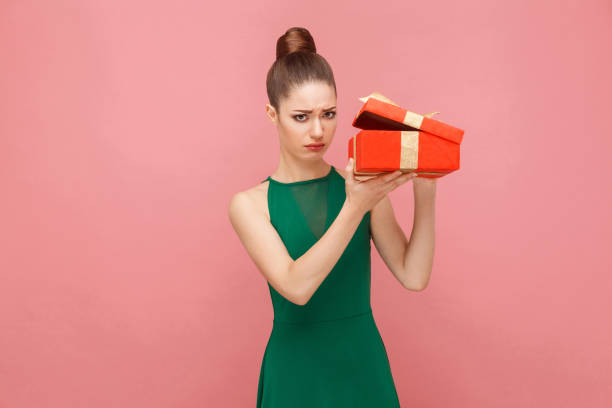woman unboxing red gift box looking inside, ahve sadness look - diabolic stock pictures, royalty-free photos & images