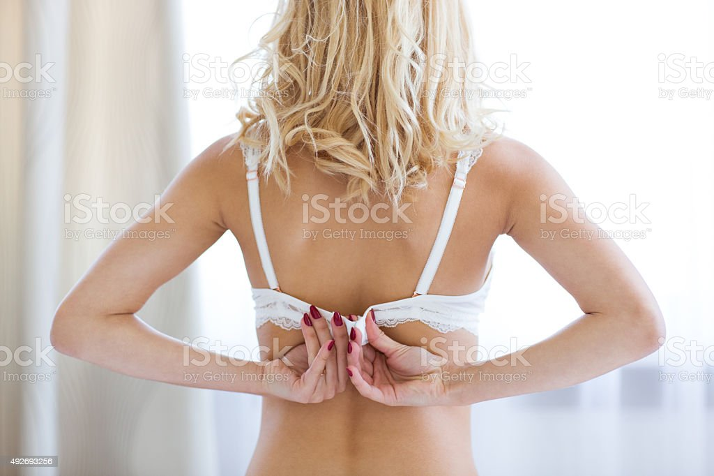 Woman unbuttoning brassiere stock photo