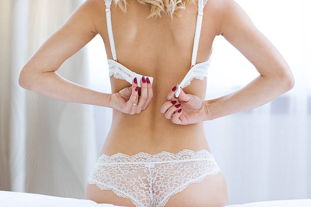 woman unbuttoning brassiere - underwear stock photos and pictures