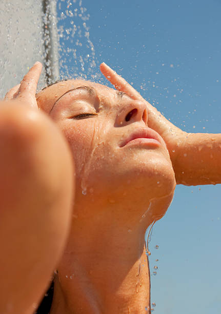woman under outdoor shower stock photo