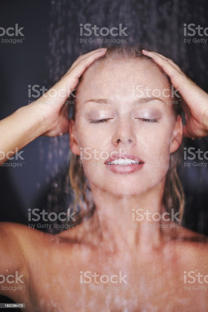 Woman under the shower against dark background royalty-free stock photo