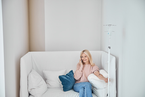 Merry female patient with a cellular phone sitting on the sofa during the medical procedure