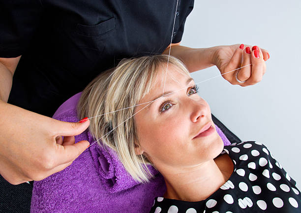 Woman undergoing threading hair removal procedure beautician makes threading hair removal procedure to blond woman in salon threading stock pictures, royalty-free photos & images