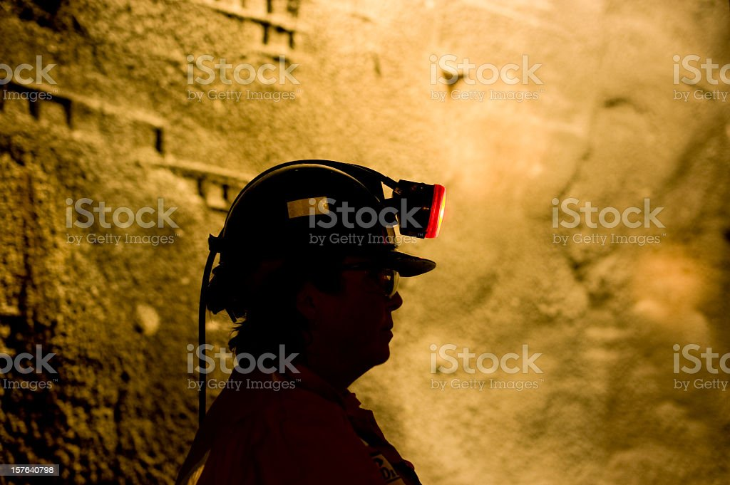 Woman Underground Mine Worker with Lamp On. stock photo