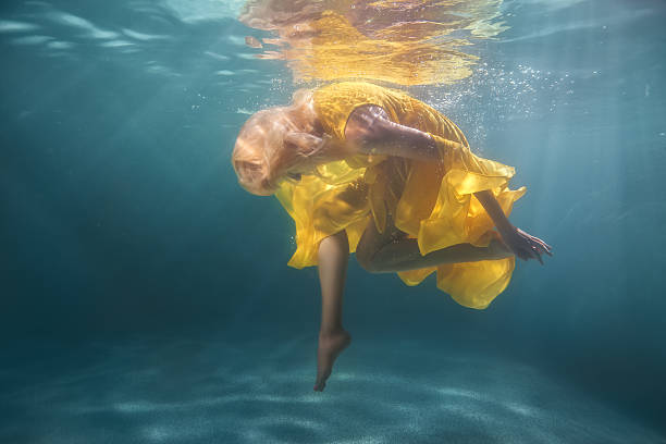 woman underwater shows figures. - meerjungfrau kleid stock-fotos und bilder