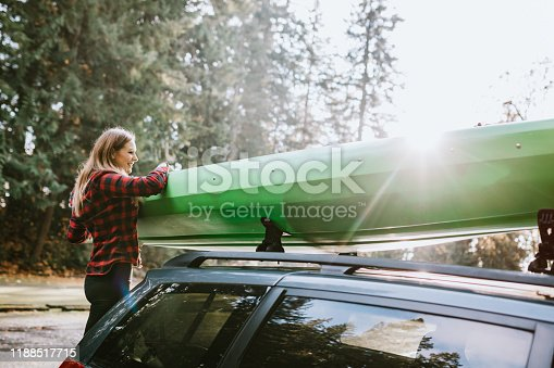 A young woman explores the beauty of Washington state, preparing to take her kayak from her car to paddle the salt water of the Puget Sound.  She unfastens straps securing the kayak to the vehicle.  Shot in Gig Harbor, WA.