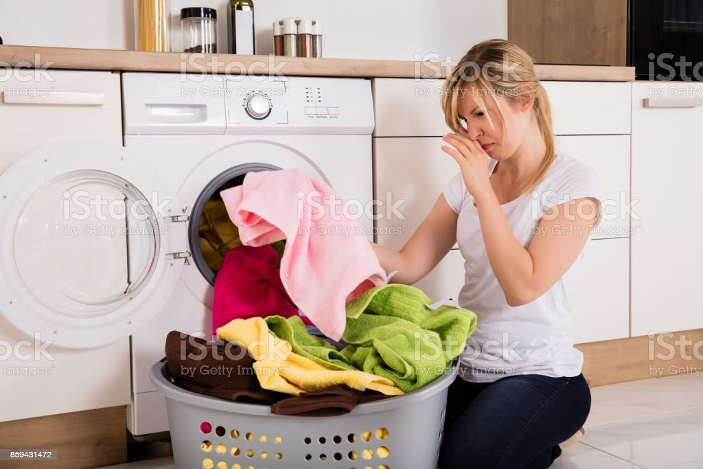 Woman Unloading Smelly Clothes From Washing Machine stock photo