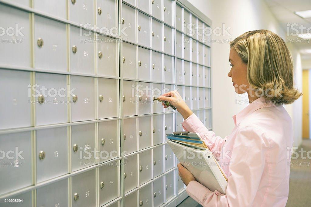 Woman unlocking a mailbox stock photo