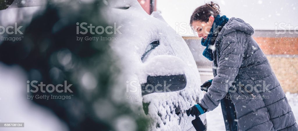 Woman wearing grey winter jacket and leather hand gloves unlocking...
