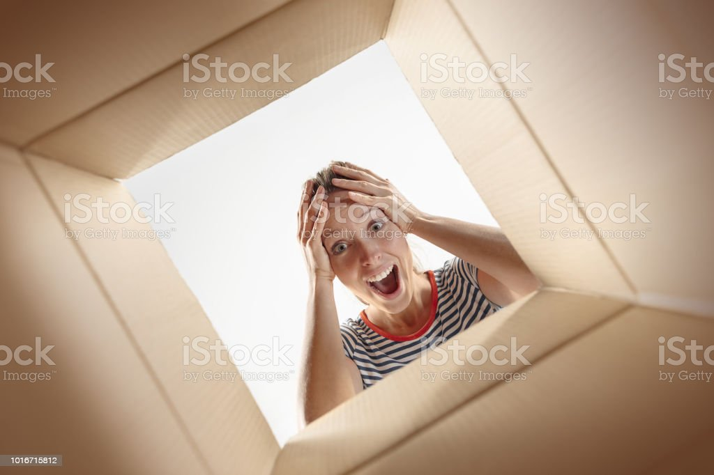 The surprised woman unpacking, opening carton box and looking inside....