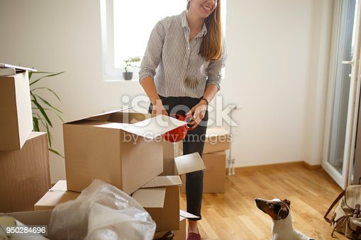 istock Woman unpacking boxes with her best friend 950284696