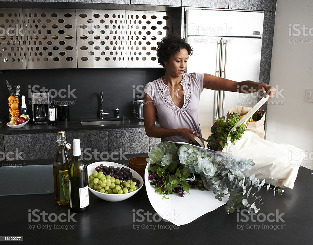 Woman Unpacking groceries in modern kitchen royaltyfri bildbanksbilder