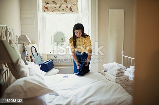 Woman unpacking in a hotel room while away on a business trip.