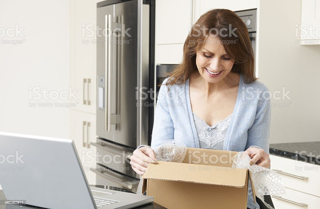 Woman Unpacking Online Purchase At Home stock photo