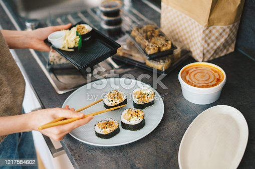 Woman placing takeaway sushi rolls from a plastic container on plate