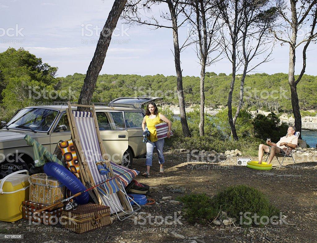 Woman unpacks car on camp site royalty free stockfoto