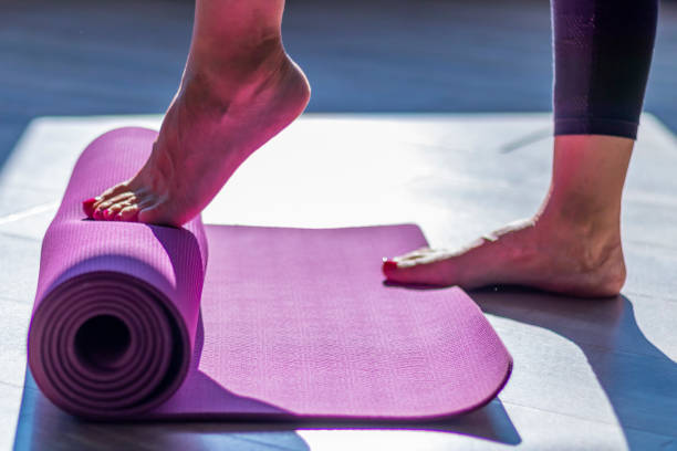 Woman unrolling yoga mat with her tiptoes Woman feet on mat yoga instructor stock pictures, royalty-free photos & images
