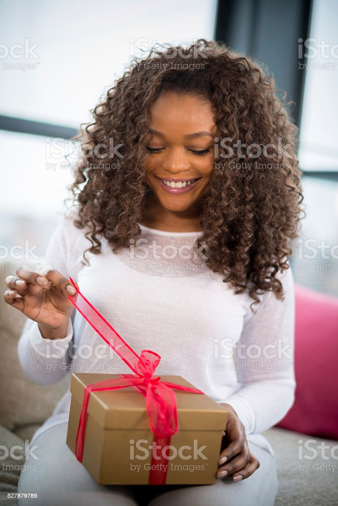 Woman unwrapping a gift stock photo