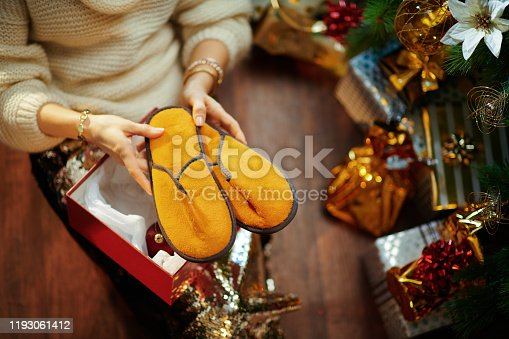 istock woman unwrapping christmas presents and got slippers 1193061412