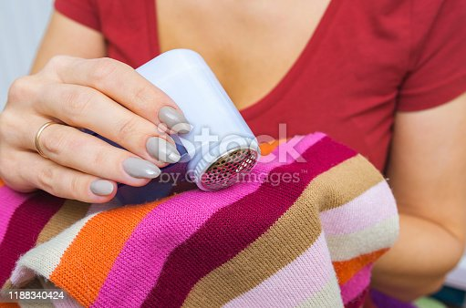 Woman use electric device for removing wool and fuzz. Wool shaver or a machine for removing lint in the hand. Close-up, selective focus.