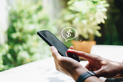 Woman use gadget mobile smartphone earn money online with dollar icon pop up. Business fintech technology on smartphone concept.