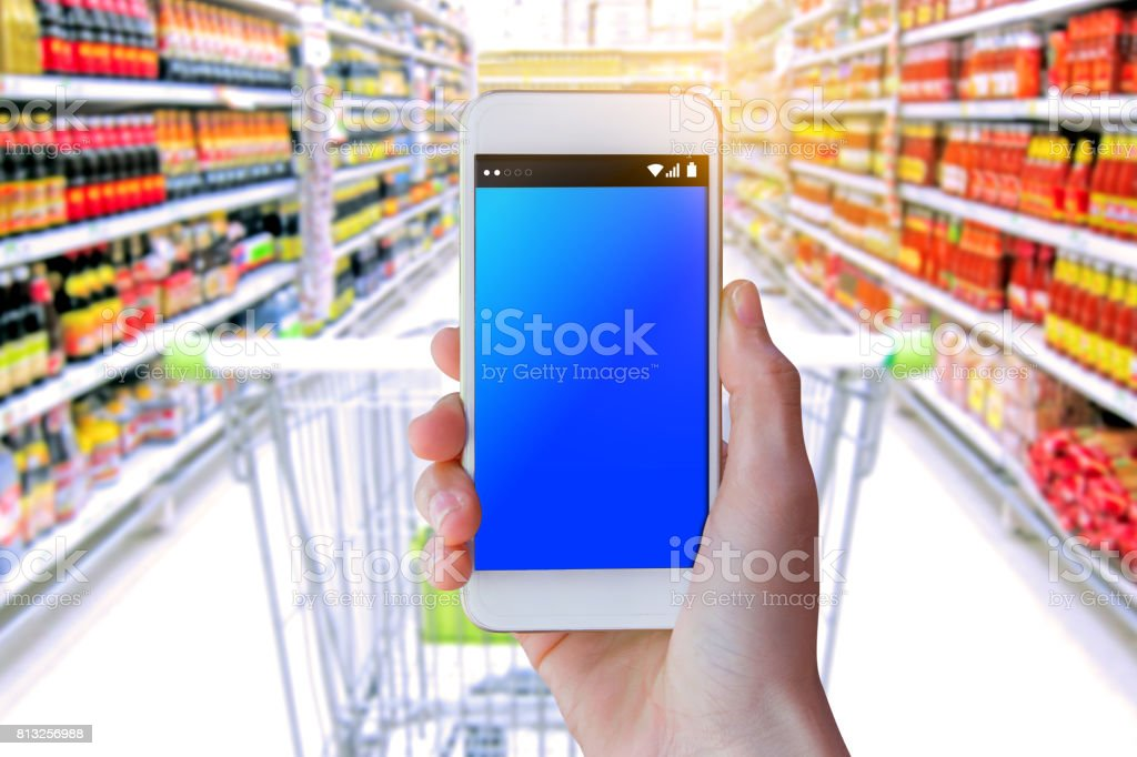 Woman use mobile phone, blur image of inside supermarket stock photo