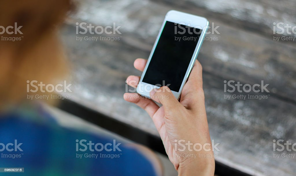 Woman use mobile phone in coffee shop from backside view. royalty-free stock photo