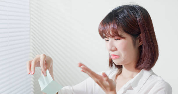 woman use oil blotting paper Young asian skin care woman upset after use oil blotting paper on her face blotting paper stock pictures, royalty-free photos & images