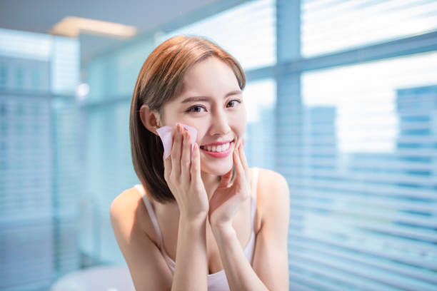 woman use oil blotting paper Young asian skin care woman smile and use oil blotting paper on her face blotting paper stock pictures, royalty-free photos & images