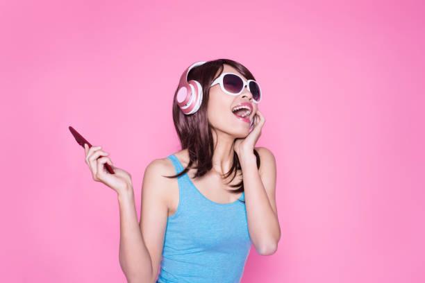vrouw telefoon luisteren muziek gebruiken - music stockfoto's en -beelden