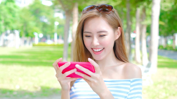 woman use phone - mobile game stock photos and pictures