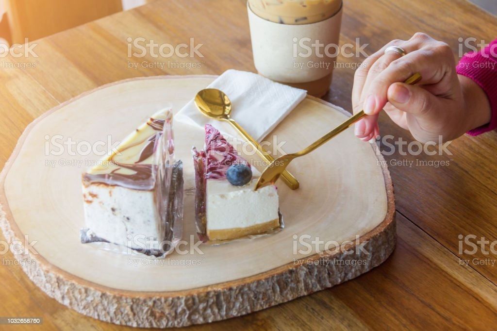 Woman use spoon to scoop blueberry cake from chopping block in cafe stock photo