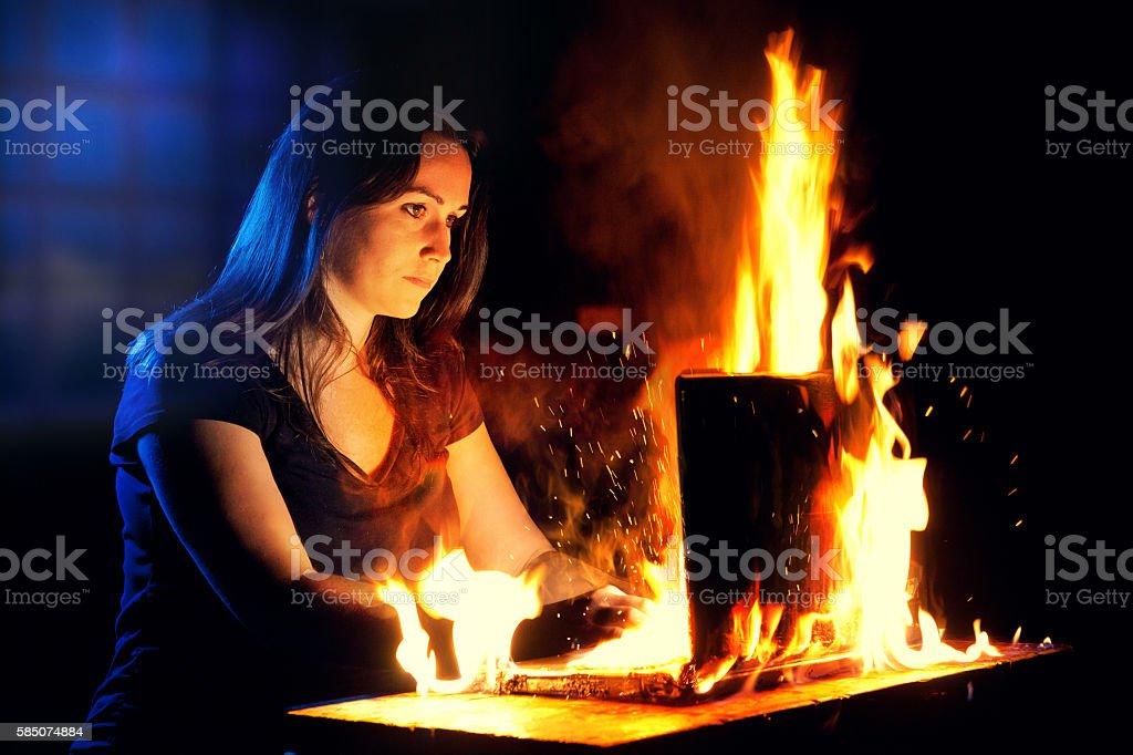 Woman uses a burning laptop stock photo