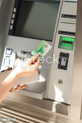 945598452 istock photo A woman uses a credit card at an ATM on the street. Operation with money. Payment. Copy space 996761748