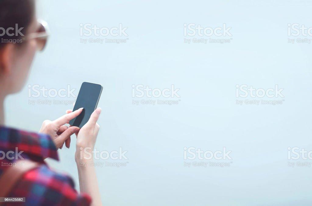 Mulher usa um smartphone sem moldura sobre o fundo de nevoeiro - Foto de stock de Adolescente royalty-free