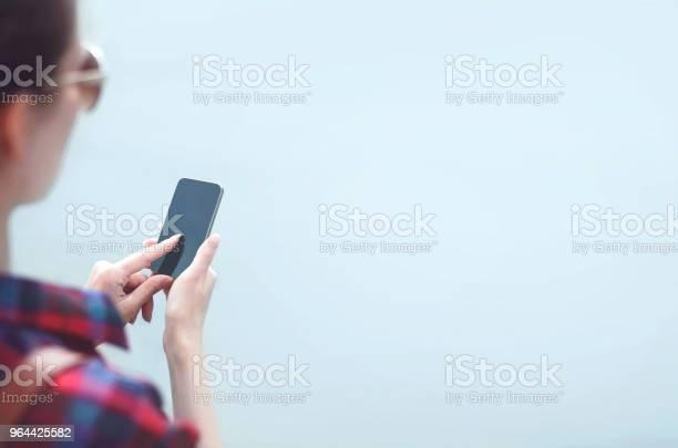 Foto de Mulher Usa Um Smartphone Sem Moldura Sobre O Fundo De Nevoeiro e mais fotos de stock de Adolescente