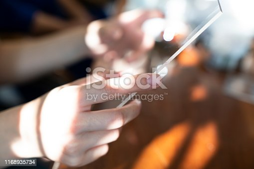 499253490istockphoto woman uses a futuristic glass phone with the latest advanced holographic technology. Concept of: future, technology, smartphone, augmented reality. 1168935734