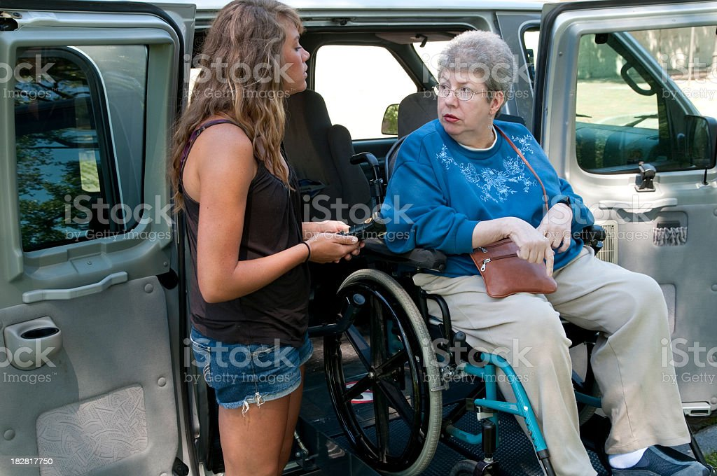 A woman uses a remote for the lift to move the wheelchair stock photo