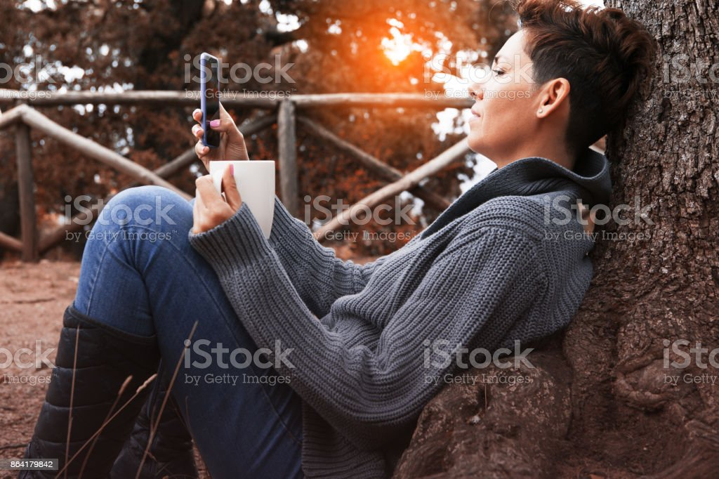 Woman uses a smartphone holding a cup in autumn forest royalty-free stock photo