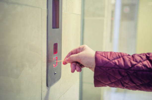 A woman uses a toothpick to avoid pressing the lift button. stock photo