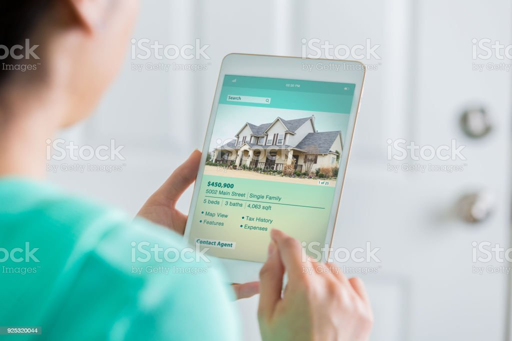 Woman uses digital table to search for new home stock photo