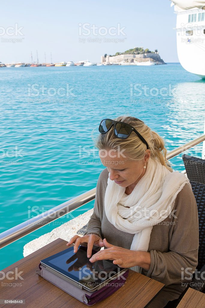 Woman uses digital tablet at harbour cafe stock photo