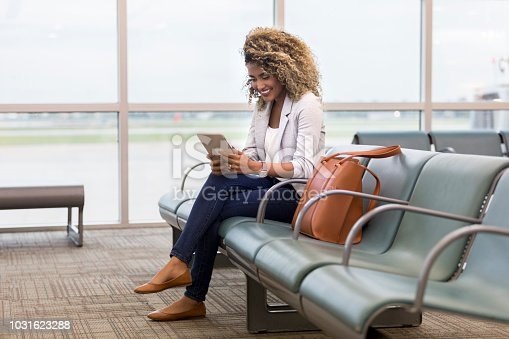 Young mixed race woman smiles cheerfully while using a digital tablet while waiting for flight in airport terminal.