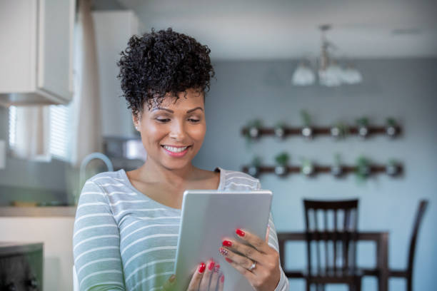 Woman uses digital tablet to call doctor for telehealth appointment stock photo