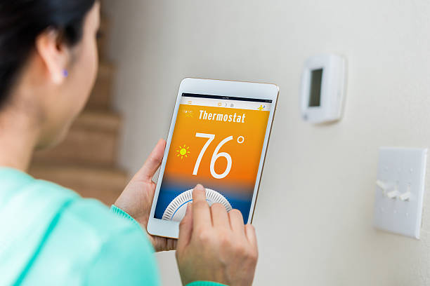 Woman uses digital tablet to control home's temperature Female homeowner uses technology on digital tabelt to control her home's temperature remotely. She is standing near the thermostat's control panel. View is over the woman's shoulder. Focus is on the digital tablet. smart thermostat stock pictures, royalty-free photos & images