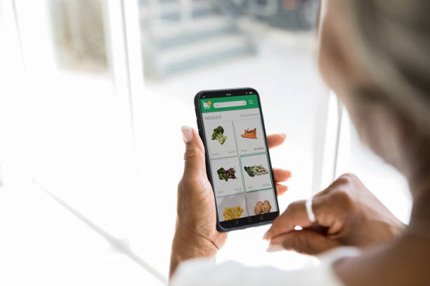 Woman uses grocery delivery app stock photo