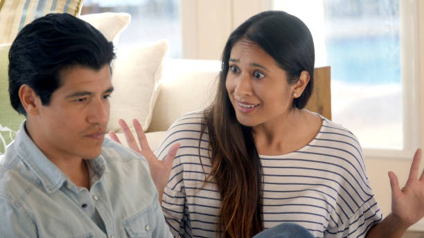 Woman uses hands to gesture in argument with her brother A woman raises up her hands in frustration with their argument, while her brother looks away annoyed. asian couple arguing stock pictures, royalty-free photos & images