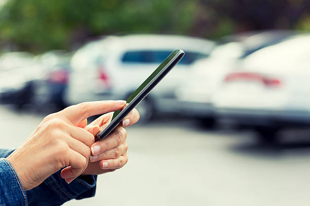 Woman uses her cell phone application connected to her car. stock photo